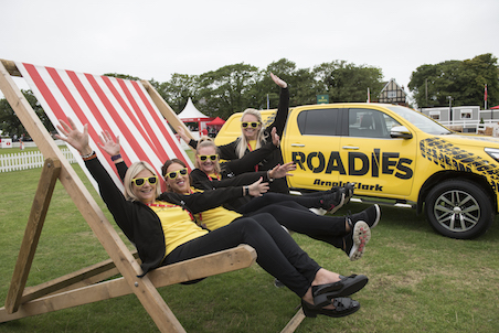 4 girls on a giant deckchair at an outdoor event