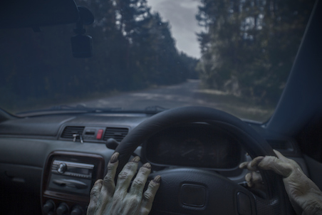 a witches hand on a steering wheel