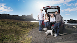 four people and a dog standing in front of a car