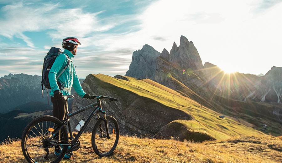 man standing with bike looking at mountains